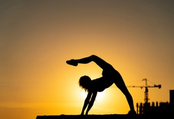 Female gymnast showing her flexibility and split during sunset on orange sky background with crane and construction. Concept of freedom and happiness