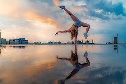 Female gymnast standing on one hand and keeping balance during dramatic sunset with reflection in the water of amazing clouds. Concept of Calisthenic, contortion and handstand