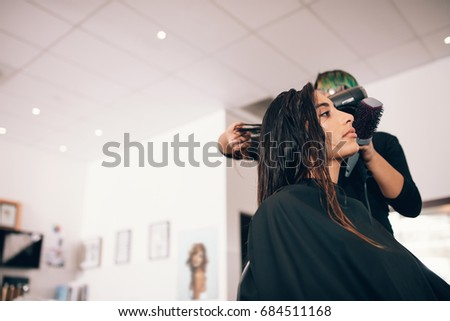 Female hair stylist using blower and brush to dry hair. Woman at a sophisticated beauty parlor getting a hairdo. #684511168