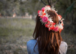 Female hair with crown of flower in nature landscape