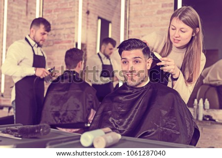 Female hairdresser cutting hair of male client with electric clipper in hair salon #1061287040