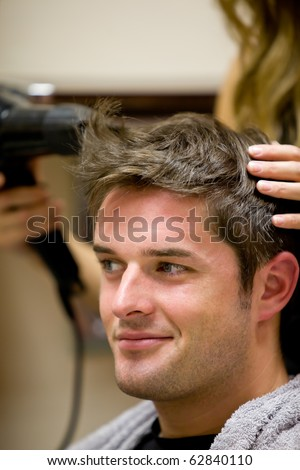 Female hairdresser drying her male customer's hair in her hairdressing salon
