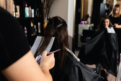 Female hairdresser makes highlights on young woman with brunette hair in salon.
