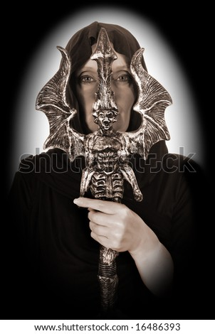 Female Halloween sorcerer, magician with ritual sword.  Studio shot - stock photo