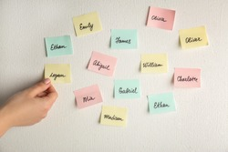 Female hand and paper stickers with different names on white wall. Concept of choosing baby name
