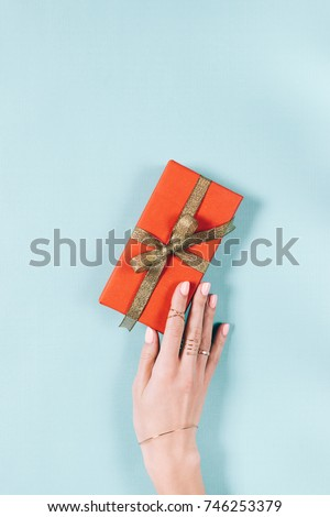 Female hand and red gift box with golden ribbon on blue background top view - Shutterstock ID 746253379