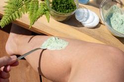 Female hand applying healing cream with Wood Fern leaves and yogurt on her leg. Traditional remedy for varicose veins. Folk medicine.