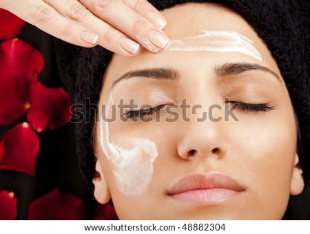 female hand applying moisturizing cream on a woman?s face
