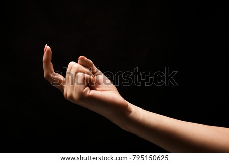 Female hand beckoning with forefinger, isolated on black background. Woman gesturing with one finger, calling up, come here symbol #795150625
