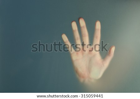 Stock Photo Female hand behind  wet glass, close-up