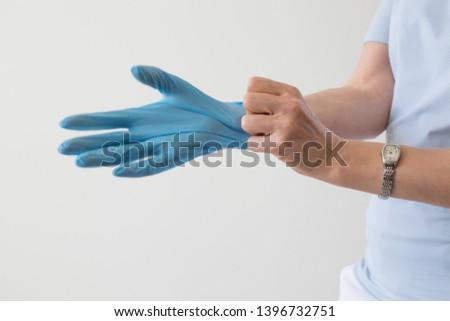 Female hand blue medical glove  closeup
