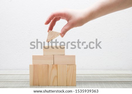 female hand builds a toy wooden house from the designer white office copy space roof
