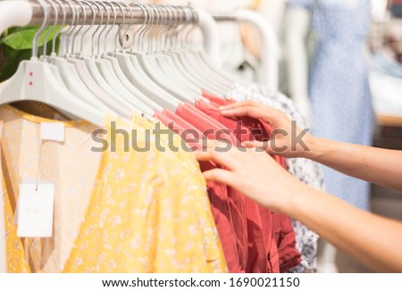 Female hand choosing clothes for checked pattern cotton dress on the rack in cloth shop at cloth shop department store. Check price, discount and promotion of clothing product.