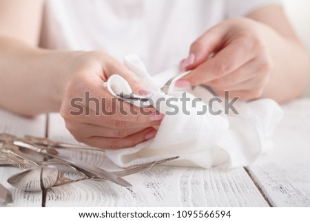 Female hand cleaning spotty silverware with a cleaning product and a cloth,Close up woman hand cleaning silver spoon,polished silver