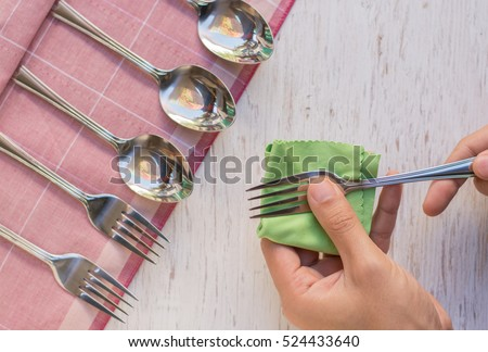 Female hand cleaning spotty silverware with a cleaning product and a cloth,Close up woman hand cleaning silver spoon,polished silver,