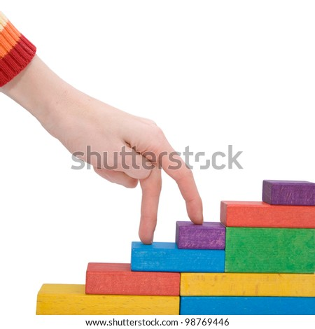 Female hand climbing upstairs which is made from wooden toy blocks.  Isolated on white background with clipping path - stock photo