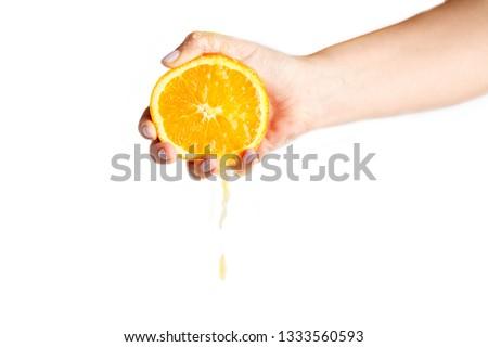 female hand crushes orange on white background. orange juice #1333560593