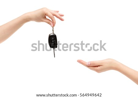 Female hand delivers car keys to other hand on a white background. #564949642
