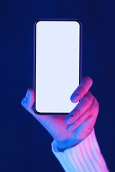 Female hand demonstrating modern smartphone with blank screen in neon blue and pink lights, vertical shot for mockup, free space, crop
