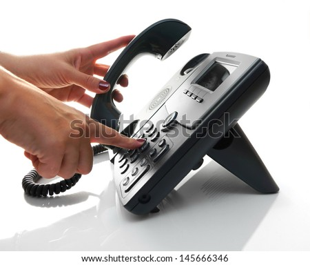 Female hand dialing a phone number with picked up headset