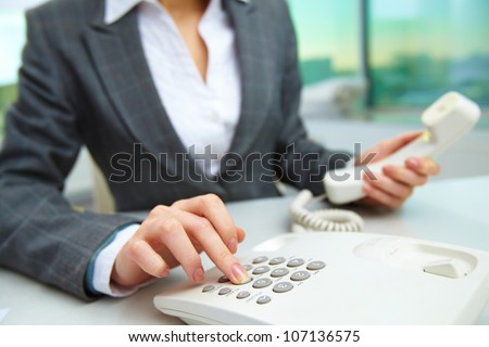 Female hand dialing number in office