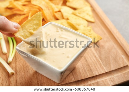 Female hand dipping nacho in bowl with beer cheese dip, closeup #608367848