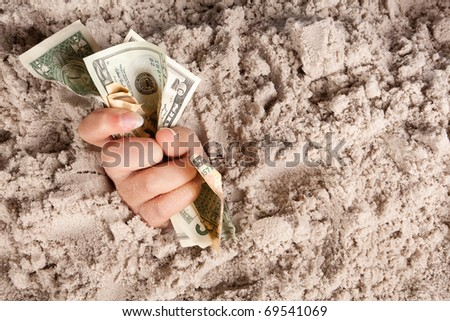 Female hand drowning in quicksand holding banknotes or money