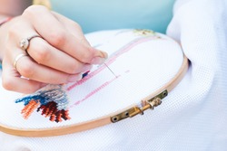 Female hand embroiders angels in the hoop, Young girl embroiders a pattern on the white material, sweetie brunette engaged in needlework
