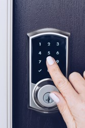 Female hand entering a code on a keypad of the front door lock