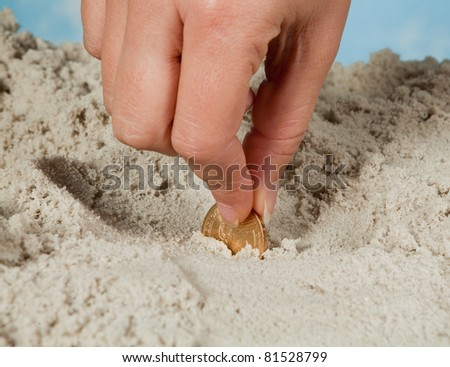 Female hand finding a copper cent or money on a sandy beach