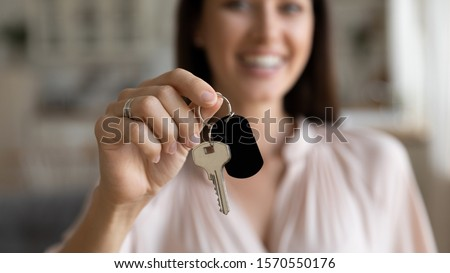 Female hand first time home owner renter customer holding house key, single woman buy real estate, mortgage loan investment, house property purchase ownership concept, close up view, focus on keyring ストックフォト ©