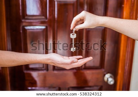 Female hand giving a key to the house a man's hand on a background of a wooden door. Owning real estate concept.