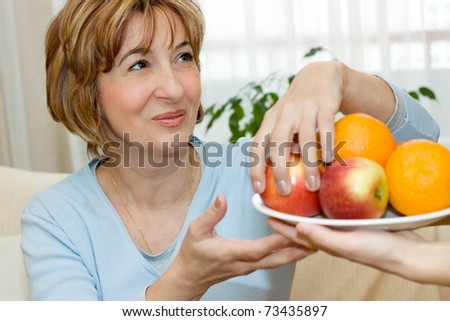 Female hand giving charming mature woman a plate with fruit.