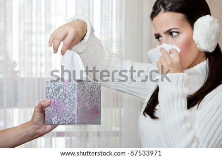 Female hand giving to young teenage girl another handkerchief from the box while she blowing her nose. Focus on the hand.