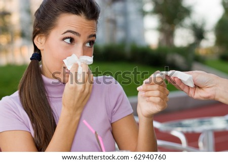 Female hand giving young teenage girl  another handkerchief while she blowing her nose.