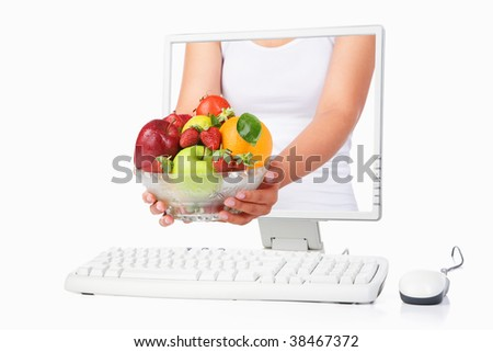 Female hand holding a bowl of fruits coming out from computer screen isolated over white background