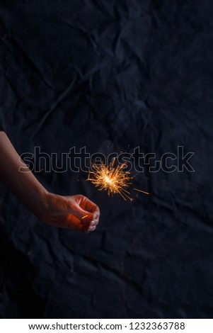 Female hand holding a burning sparkler. Christmas sparkler holiday background for xmas new year. Abstract Sparklers for celebration. #1232363788