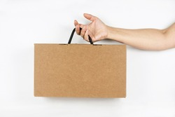 Female hand holding a cardboard box made of corrugated cardboard on a light background, place for text on the box. The woman bought shoes packed in a box
