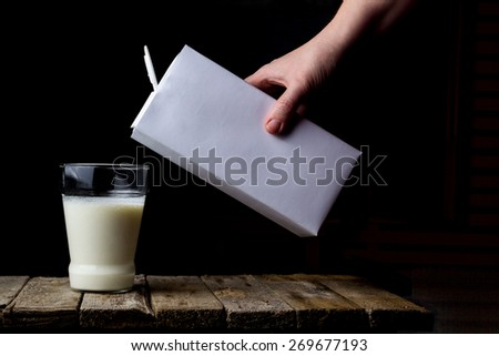 Female hand holding a carton of milk and pour into a glass on a wooden vintage background