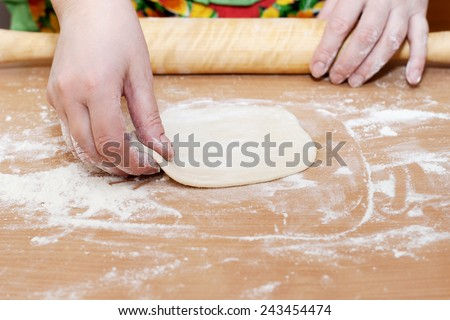 female hand holding a circle of dough kitchen table