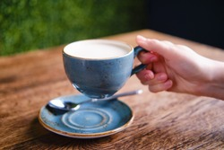 Female hand holding a cup of cappuccino coffee with milk foam in a summer cafe, close up