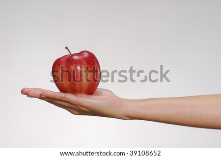 Female hand holding a fresh red apple.