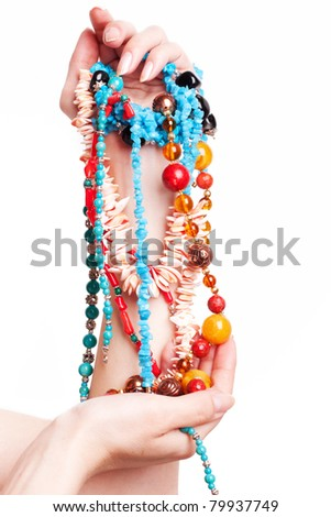 female hand holding a lot of beads