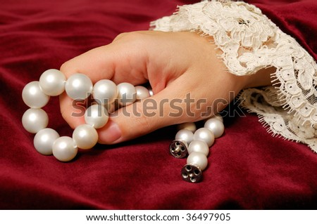 Female hand holding a  necklace from natural pearls on a red velvet surface