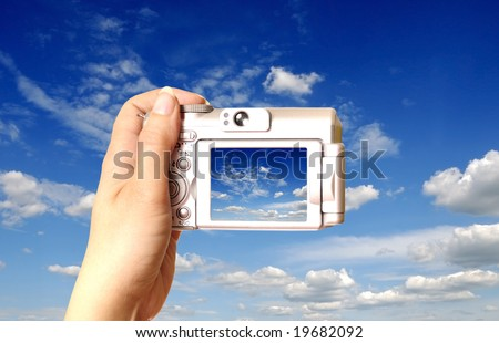 female hand holding a point and shoot camera at a blue cloudy sky