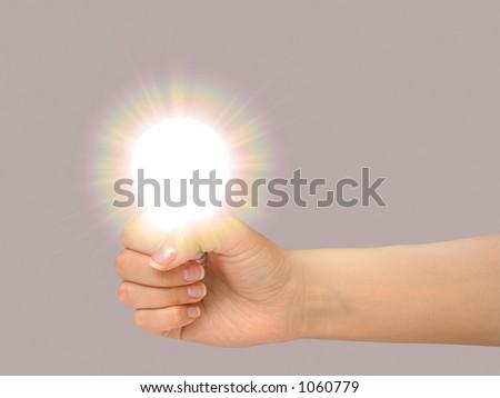 Female hand holding a shining light bulb