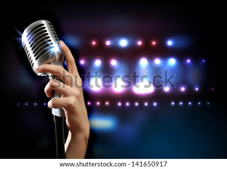 Female hand holding a single retro microphone against colourful background