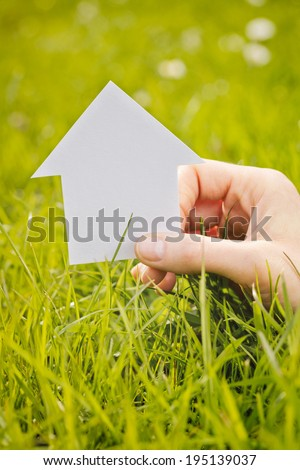 Female hand holding a small paper cutout house over a fresh green grass field.