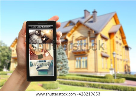 Female hand holding a smartphone on blurred house background. Home security system concept