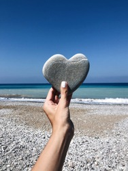 Female hand holding a stone in the shape of a heart against the background of the sea
